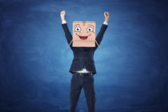 Businessman wearing a carton box with drawn happy face on blue blackboard background. Businessman with hands raised in victory and wearing a carton box with Stock Image