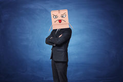 Businessman wearing carton box with painted angry face showing tongue on it Stock Photography