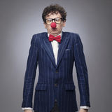 Businessman wearing clown nose. Funny businessman wearing red clown nose Stock Photo