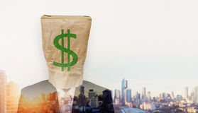 Businessman wearing crumpled brown paper bag, with green dollar sign, and double exposure cityscape in sunrise Stock Photography