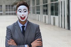 Businessman wearing a disturbing mask with arms crossed.  Stock Photo