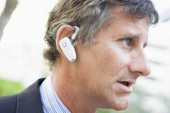 Businessman wearing earpiece outdoors Stock Photo