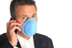 Businessman wearing a flu mask. Man on the phone while wearing a flu mask royalty free stock photography