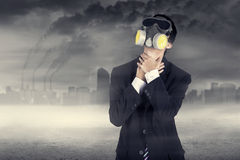 Businessman wearing a gas mask. Holding his neck Royalty Free Stock Image