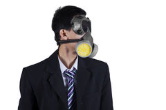 Businessman wearing gas mask isolated. Photo of a young businessman wearing a gas mask and formal suit in the studio, isolated on white background Stock Photos