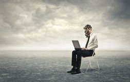 Businessman wearing a gas mask. Businessman working on a laptop wearing a gas mask Royalty Free Stock Images