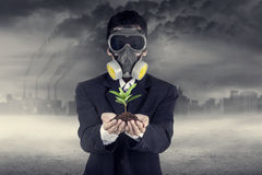 Businessman wearing a gask mask with plant Stock Images