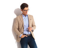 Businessman wearing glasses with hand in pocket. Side portrait of businessman wearing glasses with hand in pocket, posing looking down in isolated studio Royalty Free Stock Photo