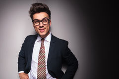 Businessman wearing glasses holding hands on waist. Smiling young businessman wearing glasses holding hands on waist and looks to side in studio Royalty Free Stock Images