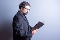 Businessman Wearing Glasses Reading from Tablet Stock Photography
