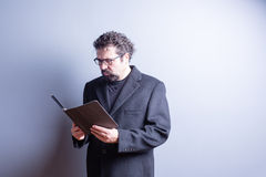 Businessman Wearing Glasses Reading from Tablet Royalty Free Stock Images