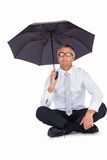 Businessman wearing glasses sheltering with umbrella. On white background Royalty Free Stock Photo