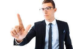 businessman wearing glasses and suit, touching an imaginary screen, presses an imaginary button on white background stock photography