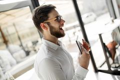 Businessman wearing glasses using tablet. Handsome businessman in shirt wearing glasses using tablet pc Stock Images