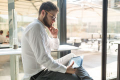 Businessman wearing glasses using tablet. Handsome businessman in shirt wearing glasses using tablet pc Stock Photos