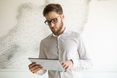 Businessman wearing glasses using tablet Royalty Free Stock Photography