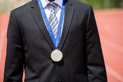 Businessman wearing gold medal. Mid section of businessman wearing gold medal and standing on running track Royalty Free Stock Photos