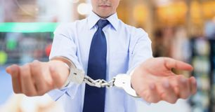 Businessman wearing handcuffs Stock Photos
