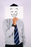 Businessman Wearing Happy Laughing Face Mask. Young Businessman Wearing Happy Laughing Face Mask Royalty Free Stock Images