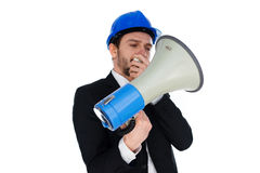 Businessman wearing a hardhat holding a megaphone. As he prepares to make a public announcement or issue instructions Royalty Free Stock Photography