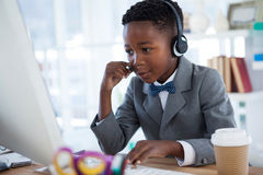 Businessman wearing headphone while using computer Royalty Free Stock Images