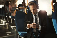 Businessman wearing headphones and reading text messages on a bu stock photos