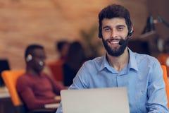 Businessman Wearing Headphones Working On Laptop In Office Stock Photos
