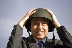 Businessman wearing helmet. A portrait view of a businessman adjusting a steel helmet or hard hat on his head.  Theme: An executive or businessperson getting Royalty Free Stock Photo