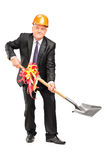 Businessman wearing helmet and holding a shovel with ribbon Stock Image