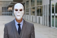 Businessman wearing a horrible mask royalty free stock image