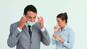 Businessman wearing a mask because a colleague is sneezing stock footage