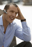 Businessman wearing mobile phone hands-free device on ear, smiling, close-up, outdoors Royalty Free Stock Photo