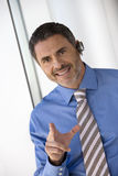 Businessman wearing mobile phone hands-free device, making hand sign, smiling, portrait (tilt) Royalty Free Stock Photo