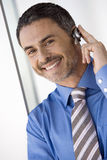 Businessman wearing mobile phone hands-free device, smiling, close-up, portrait (tilt) Stock Image