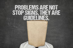 Businessman Wearing Paperbag In Head Under Slogan On Blackboard. Businessman wearing paperbag in head under problems are not stop signs, they are guidelines text Stock Photos