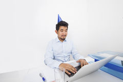 Businessman wearing party hat while using laptop in office Stock Photography