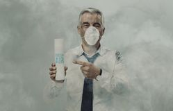 Businessman advertising a spray air purifier. Businessman wearing a pollution mask surrounded by smog, he is advertising a spray air purifier royalty free stock photo