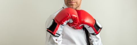Businessman wearing red boxing gloves in a defensive position. Wide view image of businessman wearing red boxing gloves in a defensive position. Over grey stock photo