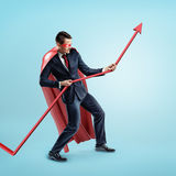 A businessman wearing a red superhero cape trying to hold a red statistic arrow with force on blue background. stock photos