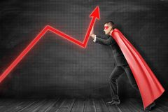 Businessman wearing red superman mask and cloak holding red diagram arrow up on black background stock photography