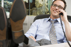 Businessman wearing spectacles, sitting in office with feet up on desk, using telephone, smiling Royalty Free Stock Photo