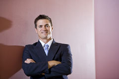 Businessman wearing suit with arms folded Royalty Free Stock Photos