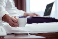 Businessman wearing suit lying on bed while drinking some tea. Some tea. Businessman wearing suit lying on bed while drinking some tea and working on his laptop royalty free stock photos