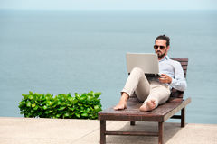 Businessman wearing a suit using laptop on the beach Royalty Free Stock Photography