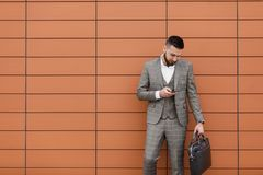 Businessman wearing suit and using modern smartphone near office at early morning, successful employer to make a deal Stock Image