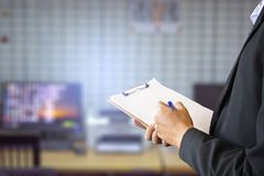 Businessman wearing suit writing on notepad and blurry background stock photo
