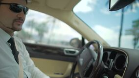Businessman wearing sunglasses driving expensive automobile, transportation. Stock footage stock video footage