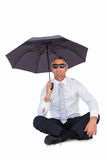 Businessman wearing sunglasses and sheltering with umbrella. On white background Stock Images