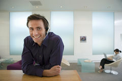 Businessman wearing telephone headset, leaning on counter in reception area, smiling, portrait, woman using laptop in background,  Royalty Free Stock Images