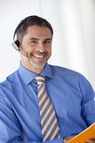 Businessman wearing telephone headset, smiling, portrait (tilt) Royalty Free Stock Photo